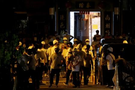 Men in white T-shirts and carrying poles are seen in Yuen Long after attacking anti-extradition bill demonstrators at a train station in Hong Kong