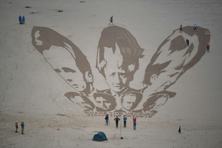 A sand drawing of the G7 leaders in Cornwall by activists who called on nations to 'share the vaccine and waive the patents'