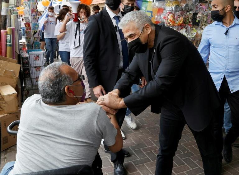 Israeli opposition leader Yair Lapid presses the flesh in the coastal city of Hod Hasharon, taking advantage of the country's world-beating coronavirus vaccination campaign to make a final face-to-face push for votes