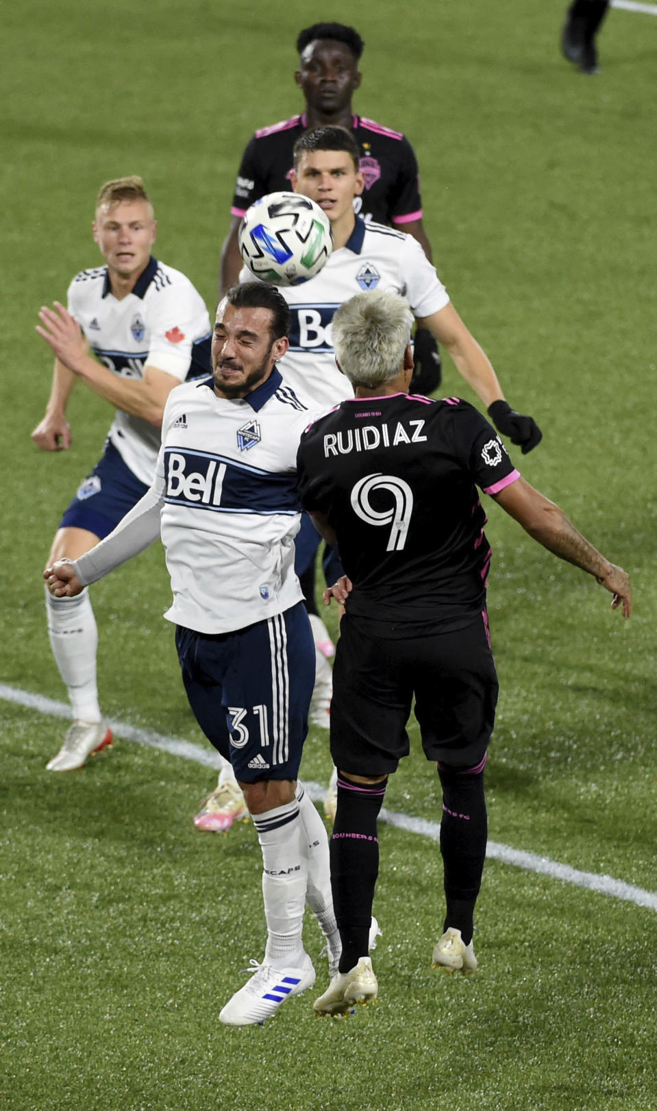 Vancouver Whitecaps midfielder Russell Teibert, left, and Seattle Sounders forward Raul Ruidiaz jump for a head ball during the first half of an MLS soccer match in Portland, Ore., Tuesday, Oct. 27, 2020. (AP Photo/Steve Dykes)