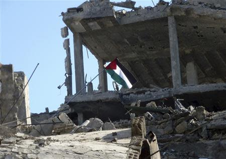 A Palestinian flag flutters atop a damaged building at the Palestinian refugee camp of Yarmouk, south of Damascus, February 12, 2014. Picture taken February 12, 2014. REUTERS/Mohamad Mohamad