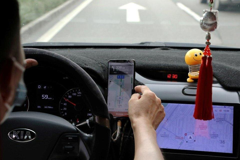 A driver of Chinese ride-hailing service Didi drives with a phone showing a navigation map on Didi's app in Beijing on July 5. Experts say Chinese authorities could be concerned about the exposure risks of sensitive data collected by Didi and similar services. Photo: Reuters