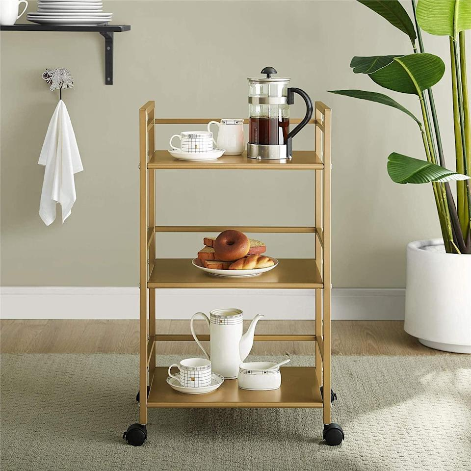 <p>Whether you want to create a mini kitchen and coffee station or need a place to store your beauty must haves, this stunning <span>Novogratz Helix Utility Cart, Gold</span> ($48, originally $56) will come in handy. Use the three shelves to store all of your snacks, cleaning supplies, or books.</p>