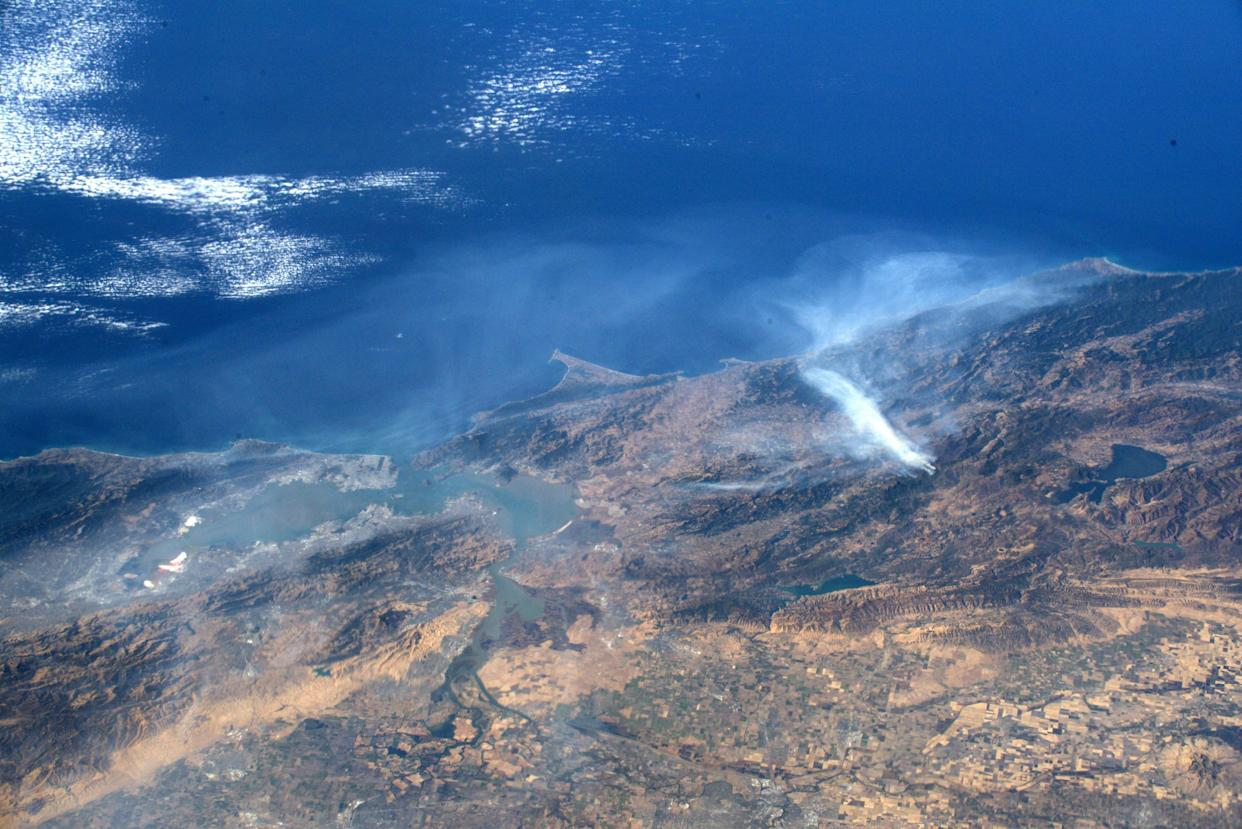 This undated handout image, courtesy of NASA and taken by astronaut Andrew Morgan aboard the International Space Station, shows smoke from the Kincade Fire (right) in Sonoma County, northern California. San Francisco is at the left.