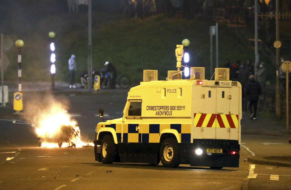 The Police Service of Northern Ireland comes under attack by Loyalists at the Cloughfern roundabout in Newtownabbey, Belfast, Northern Ireland, Saturday, April 3, 2021. Masked men threw petrol bombs and hijacked cars in the Loyalist area North of Belfast. Loyalists and unionists are angry about post-Brexit trading arrangements which they claim have created barriers between Northern Ireland and the rest of the UK. (Peter Morrison/PA via AP)