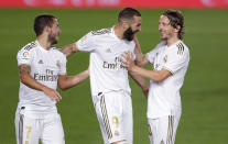 Real Madrid's Karim Benzema, center, celebrates with his teammates Eden Hazard, left, and Luka Modric after scoring his side's opening goal during the Spanish La Liga soccer match between Real Madrid and Valencia at Alfredo di Stefano stadium in Madrid, Spain, Thursday, June 18, 2020. (AP Photo/Manu Fernandez)