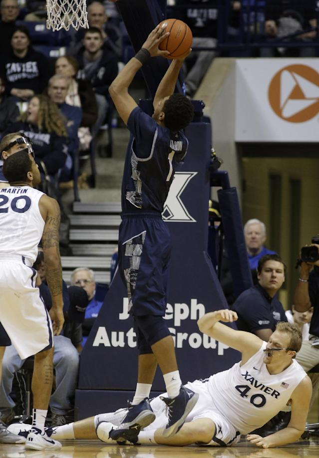 Georgetown forward Reggie Cameron (1) shoots against Xavier forward Justin Martin (20) and center Matt Stainbrook (40) in the first half of an NCAA college basketball game on Wednesday, Jan. 15, 2014, in Cincinnati. (AP Photo/Al Behrman)