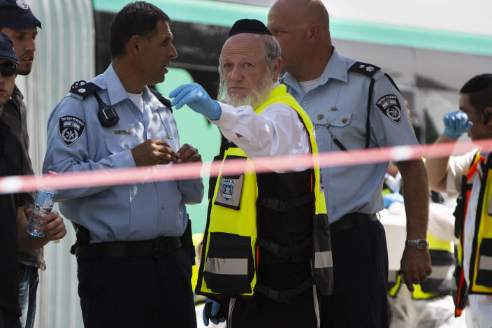 FILE - In this Oct. 13, 2015 file photo, Yehuda Meshi-Zahav, then head of Israel's ZAKA rescue service, center, stands stands at the scene of a shooting attack by a Palestinian gunman, in Jerusalem. On Sunday, March 14, 2021, the Israeli police announced that the force's major crimes unit, Lahav 433, had opened an investigation into sexual abuse allegations against Meshi-Zahav. In recent days, some 20 people have come forward with claims that he was a savage sexual predator who assaulted men, women and children for years. (AP Photo Oded Balilty, File)