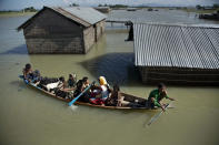 """FILE - In this July 31, 2016, file photo, a flood-affected family with their goats travel on a boat in the Morigaon district, east of Gauhati, northeastern Assam state, India. Climate change could push more than 200 million people to move within their own countries in the next three decades and create migration hotspots unless urgent action is taken in the coming years to reduce global emissions and bridge the development gap, a World Bank report has found. The report published on Monday, Sept. 13, 2021 examines how long-term impacts of climate change such as water scarcity, decreasing crop productivity and rising sea levels could lead to millions of what the report describes as """"climate migrants"""" by 2050. (AP Photo/Anupam Nath, File)"""