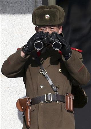 A North Korean soldier, with a pair of binoculars, observes activity in the south of the truce village of Panmunjom in the demilitarised zone separating the two Koreas, north of Seoul February 6, 2014.REUTERS/Han Jae-ho/News1