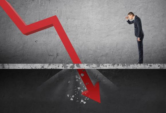 Man in suit looks at red line on a chart falling sharply through the floor.