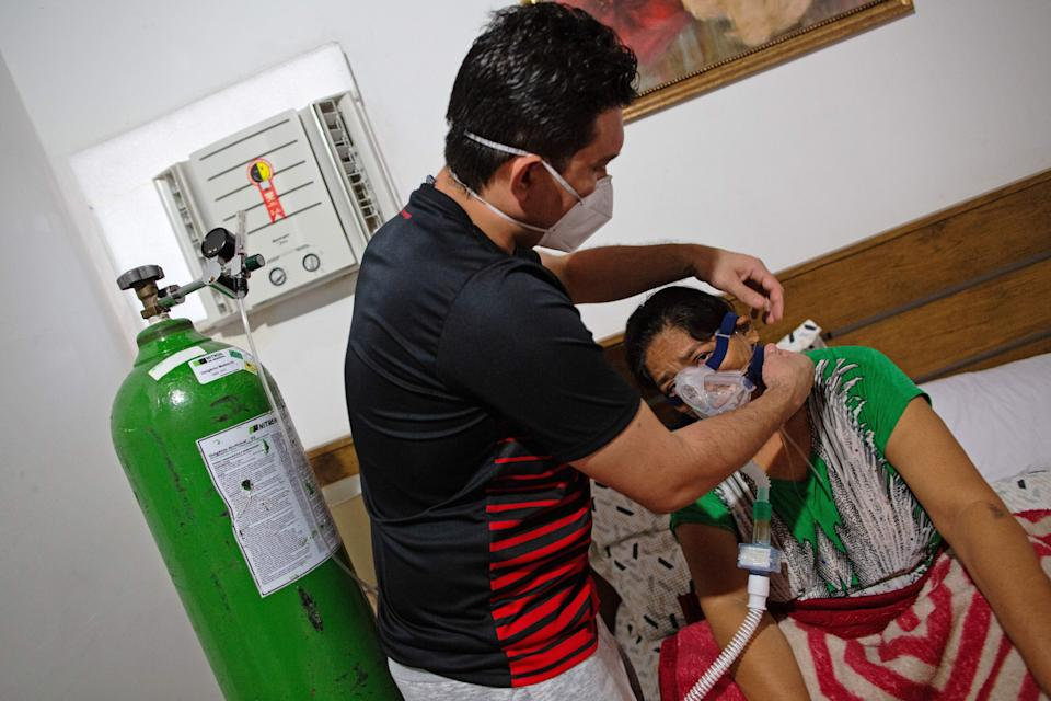 Brazilian emergency doctor Marcos Fonseca Barbosa (L) helps his mother Ruth Fonesca, 56, at his home in Manaus, Amazonas state, Brazil on January 10, 2021. - Marcos was forced to treat his own mother at his home even though she has severe COVID-19 symptoms, due to a shortage of hospital beds in the city, as cases increased at an alarming rate. Manaus, with its two million inhabitants, had already experienced nightmarish scenes in April and May, with mass graves and refrigerated trucks parked in front of hospitals to pile up the dead. But the situation is even worse in the beginning of 2021, since between January 1 and 11, at least 1,979 people were admitted to hospitals due to the virus, against 2,128 for the whole month of April, the worst since the start of the pandemic. (Photo by MICHAEL DANTAS / AFP) (Photo by MICHAEL DANTAS/AFP via Getty Images)