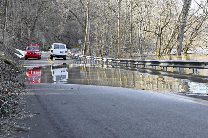 Road crews and members of the Frankfort, Ky., fire department block traffic from traveling on Big Eddy Road as the Kentucky River washes over the roadway in Frankfort, Ky., Tuesday, March 2, 2021. (AP Photo/Timothy D. Easley)