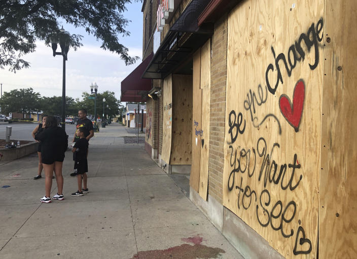 Residents stand in front of boarded-up businesses in Kenosha, Wis., Thursday, Aug. 27, 2020, days after protests of the police shooting of Jacob Blake turned violent and demonstrators set fire to a number of buildings. (AP Photo/Russell Contreras)