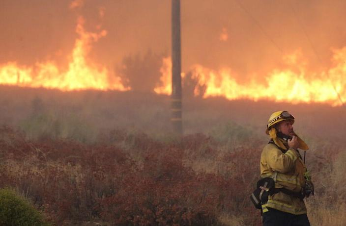 A firefighter works near flames as the Bobcat Fire burns on September 18, 2020 in Juniper Hills, California. Numerous homes were destroyed in the area a day after mandatory evacuations there as the Bobcat Fire has now scorched more than 72,000 acres. California's national forests remain closed due to wildfires which have burned a record 3.4 million acres this year. (Photo by Mario Tama/Getty Images)