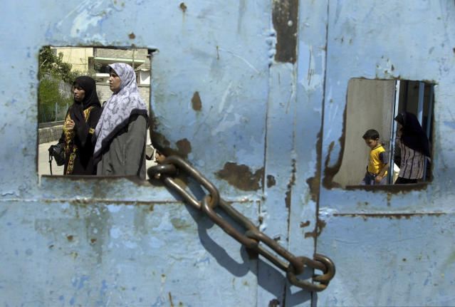 <p>Palestinians leave a United Nations health clinic, with its main vehicle gate chained closed, at the Jabalia refugee camp, home to over 101,000 refugees, in the northern Gaza Strip, Aug. 20, 2002. (Photo: Jacqueline Larma/AP) </p>