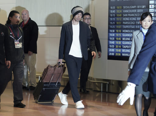Seattle Mariners' Ichiro Suzuki, center, walks upon his team's arrival at Haneda international airport in Tokyo Friday, March 15, 2019. The Mariners will play in a two-baseball game series against the Oakland Athletics to open the Major League season on March 20-21 at the Tokyo Dome. (AP Photo/Eugene Hoshiko)