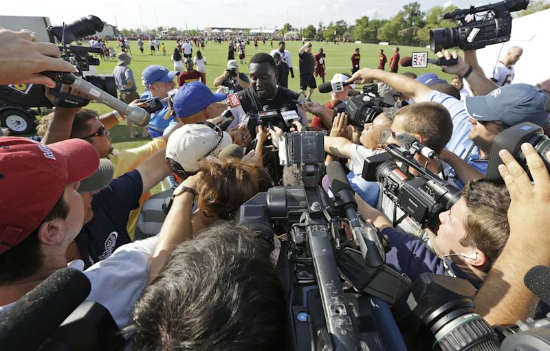 Washington Redskins defensive end Jarvis Jenkins, center, faces reporters after the second day of the NFL football team's training camp in Richmond, Va. Friday, July 26, 2013. Jenkins was suspended for four games without pay Friday for violating the NFL's drugs policy. (AP Photo/Steve Helber)