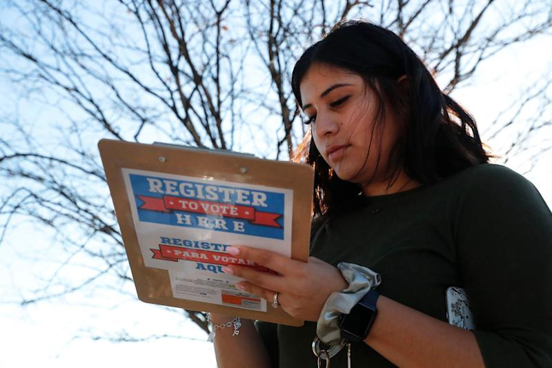 Karina Shumate, 21, a college student studying stenography, fills out a voter registration form in Richardson, Texas, Saturday, Jan. 18, 2020. Democrats are hoping this is the year they can finally make political headway in Texas and have set their sights on trying to win a majority in one house of the state Legislature. Among the hurdles they'll have to overcome are a series of voting restrictions Texas Republicans have implemented in recent years, including the nation's toughest voter ID law, purging of voter rolls and reductions in polling places. (AP Photo/LM Otero)