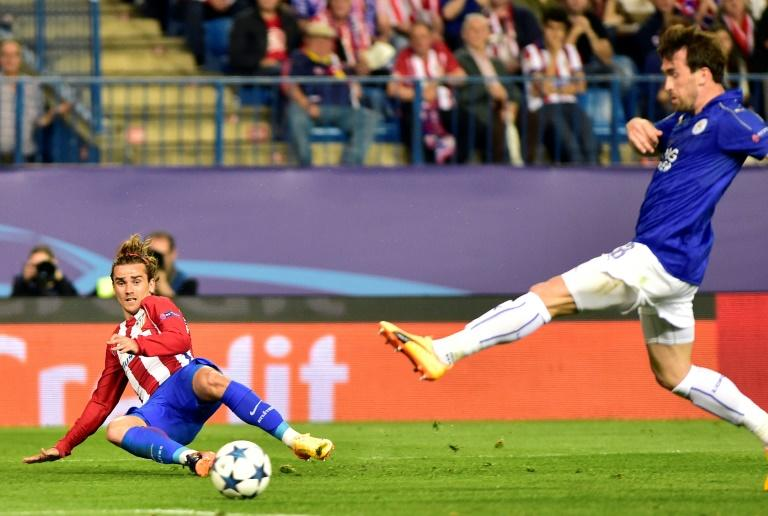 Atletico Madrid forward Antoine Griezmann (L) curls a cross in past Leicester City defender Christian Fuchs during the Champions League quarter-final first leg at the Vicente Calderon stadium in Madrid on April 12, 2017