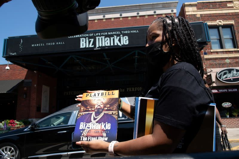 A woman displays the program during the funeral for late rapper Marcel Theo Hall, known by his stage name Biz Markie, outside Patchogue Theatre in Patchogue, New York