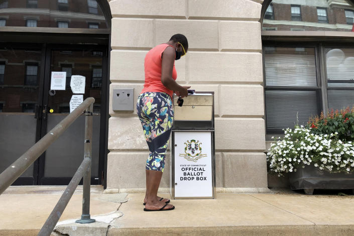 FILE - In this Aug. 6, 2020, file photo, Katrina McKelvin of New London, Conn., deposits her absentee ballot for the Aug. 11 primary in a special box that has been set up outside the New London City Hall. As Republicans roll back access to the ballot, Democratic lawmakers have been quietly moving to expand voting rights. (AP Photo/Susan Haigh, File)