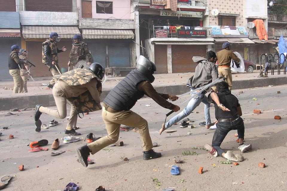 TOPSHOT - Police clash with protesters during demonstrations against India's new citizenship law in Lucknow on December 19, 2019. - Indians defied bans on assembly on December 19 in cities nationwide as anger swells against a citizenship law seen as discriminatory against Muslims, following days of protests, clashes and riots that have left six dead. (Photo by STR / AFP) (Photo by STR/AFP via Getty Images)