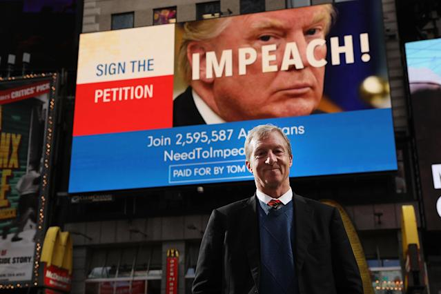 Philanthropist Tom Steyer stands in front of one of the billboards he funded in Times Square. (Photo: Spencer Platt/Getty Images)