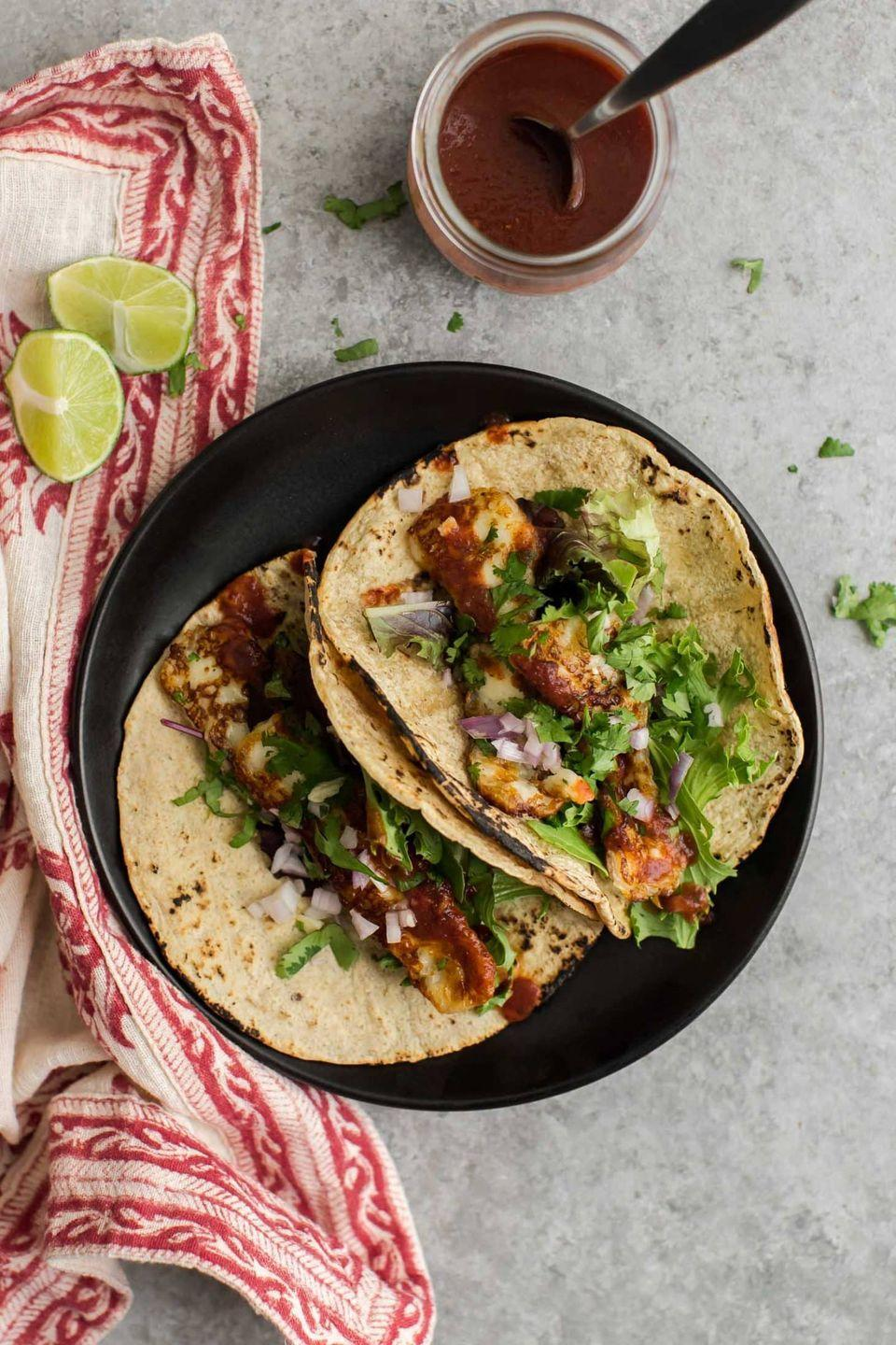 """<p>These halloumi tacos are kept deliciously simple with a few greens, fried halloumi tossed in garlic and coriander, and topped with a sprinkle of onion and hot sauce.</p><p>Get the <a href=""""https://naturallyella.com/garlicky-halloumi-tacos/"""" rel=""""nofollow noopener"""" target=""""_blank"""" data-ylk=""""slk:Garlicky Halloumi Tacos"""" class=""""link rapid-noclick-resp"""">Garlicky Halloumi Tacos</a> recipe.</p><p>Recipe from <a href=""""https://naturallyella.com/"""" rel=""""nofollow noopener"""" target=""""_blank"""" data-ylk=""""slk:Naturally Ella"""" class=""""link rapid-noclick-resp"""">Naturally Ella</a>.</p>"""