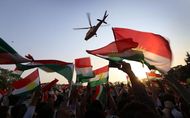 <p>A helicopter flies over an Iraqi Kurd gathering where people were being urged to vote in the upcoming independence referendum in Arbil, the capital of the autonomous Kurdish region of northern Iraq, Sept. 15, 2017. (Photo: Safin Hamed/AFP/Getty Images) </p>