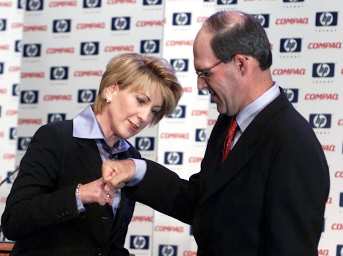 Carly Fiorina (left), chairman and CEO of Hewlett Packard, taps knuckles with Michael Capellas, chairman and CEO of Compaq, after a press conference in New York on September 4, 2001, where they discussed the announced merger of the two companies.