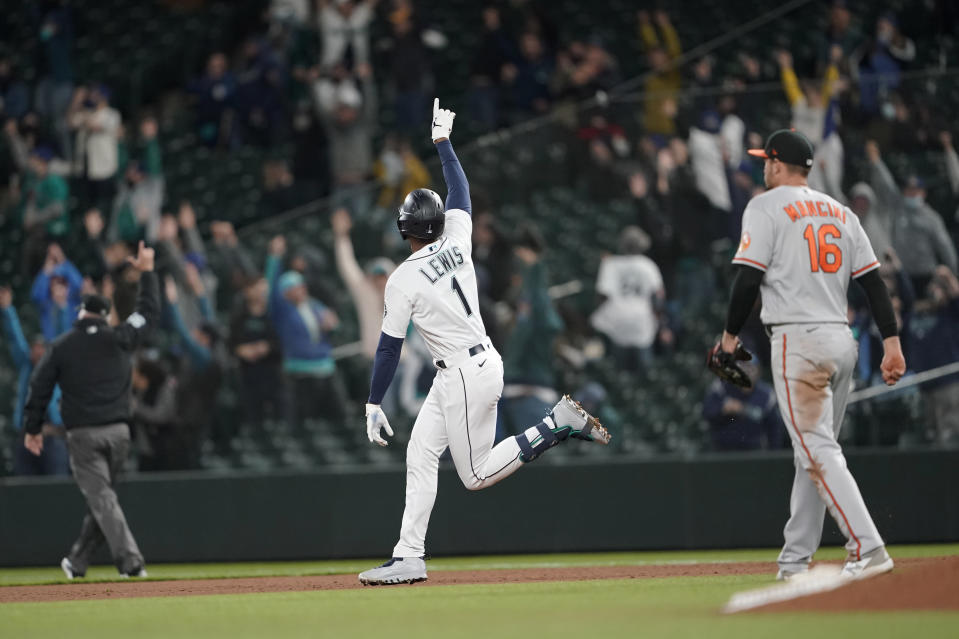Seattle Mariners' Kyle Lewis celebrates after he hit a three-run home run as Baltimore Orioles first baseman Trey Mancini looks on during the eighth inning of a baseball game, Tuesday, May 4, 2021, in Seattle. (AP Photo/Ted S. Warren)