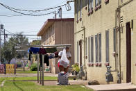 A woman hangs laundry outside a pubic housing building, Monday, Sept. 13, 2021, in Phoenix. Soaring temperatures are making it harder to live in the United States' already hot, fast growing desert areas. Heat dangers are even more pronounced in poor and racially and ethnically diverse communities in the West's burgeoning desert cities and counties, where people don't have enough protection against heat waves. (AP Photo/Matt York)