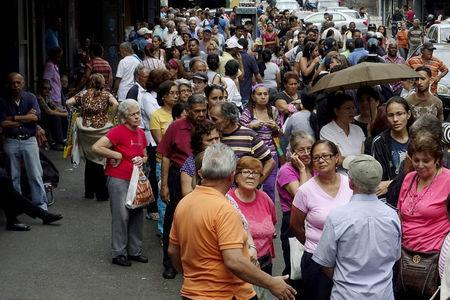 People queue to try to buy basic food items outside a supermarket in Caracas March 16, 2016. REUTERS/Carlos Garcia Rawlins/File Photo