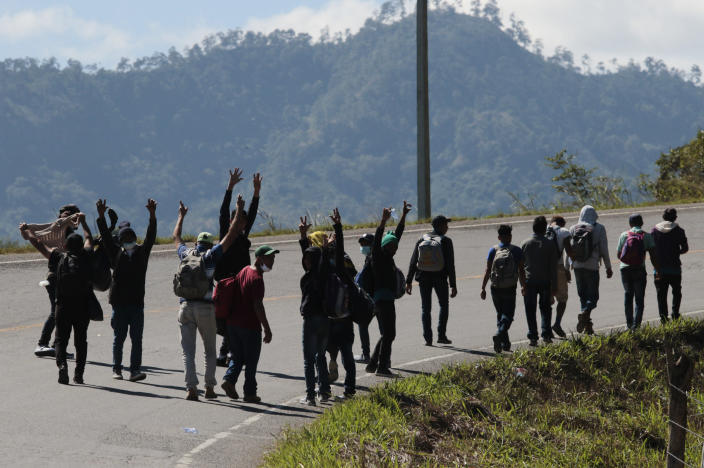 Migrants walk on the road on their way North near Agua Caliente, close to the border with Guatemala, Thursday, Dec. 10, 2020. Honduran security forces stationed on the highway a few kilometers before Agua Caliente, asked the migrants for their passports or identity cards and proof of a COVID-19 test, and if they did not produce those documents they would not be allowed to move on. (AP Photo/Delmer Martinez)