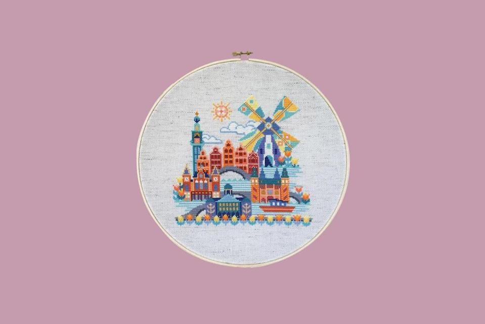 """<p>Part of their popular """"Pretty Little City"""" series, this cross stitch pattern of Amsterdam features all of the must-see landmarks including the Royal Palace of Amsterdam, the Rijksmuseum, the Westerkerk clock tower, a whimsical windmill, canals, and, of course, tulips.</p> <p><strong><em>Shop Now:</em></strong><em> Satsuma Street Pretty Little Amsterdam Cross Stitch Kit, $49.50, </em><a href=""""https://stitchedmodern.com/collections/all-cross-stitch/products/pretty-little-amsterdam-cross-stitch-pattern?variant=7040504660003"""" rel=""""nofollow noopener"""" target=""""_blank"""" data-ylk=""""slk:stitchedmodern.com"""" class=""""link rapid-noclick-resp""""><em>stitchedmodern.com</em></a><em>.</em></p>"""