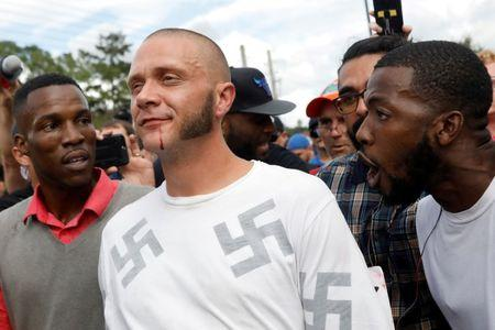 A man walks with a bloody lip as demonstrators yell at him outside the location where Richard Spencer, an avowed white nationalist and spokesperson for the so-called alt-right movement, is delivering a speech on the campus of the University of Florida in Gainesville, Florida, U.S., October 19, 2017. REUTERS/Shannon Stapleton/File photo