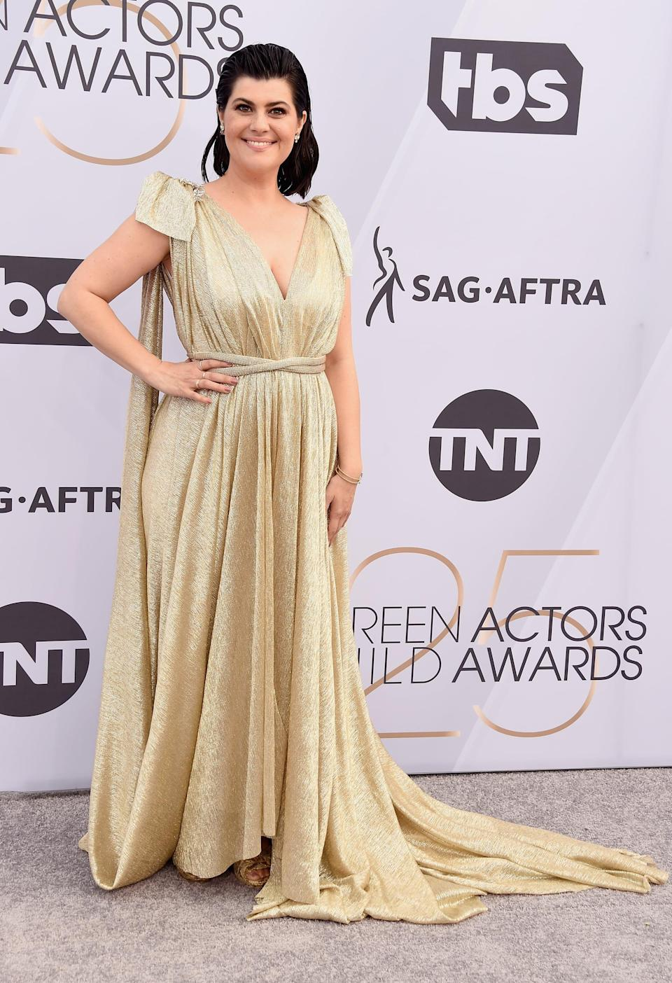 <p>Wearing a gold gown. </p>