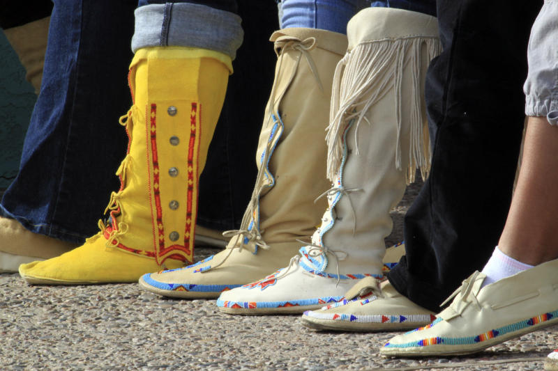 """Participants display their moccasins during the """"Rock Your Mocs"""" celebration at the Indian Pueblo Cultural Center in Albuquerque, N.M., on Friday, Nov. 15, 2013. The social media campaign started by Laguna Pueblo's Jessica """"Jaylyn"""" Atsye has gone global with Native American and indigenous people from as far away as New Zealand participating. (AP Photo/Susan Montoya Bryan)"""