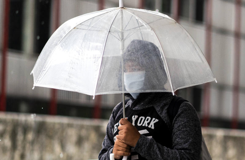 A person wears a mask as a precaution against the spread of the new coronavirus under their umbrella as it rains in Montevideo, Uruguay, Wednesday, March 18, 2020. The vast majority of people recover from the COVID-19 disease. (AP Photo/Matilde Campodonico)