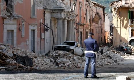 A policeman stands in front of collapsed buildings after an earthquake in Aquila, Italy, on April 7, 2009.