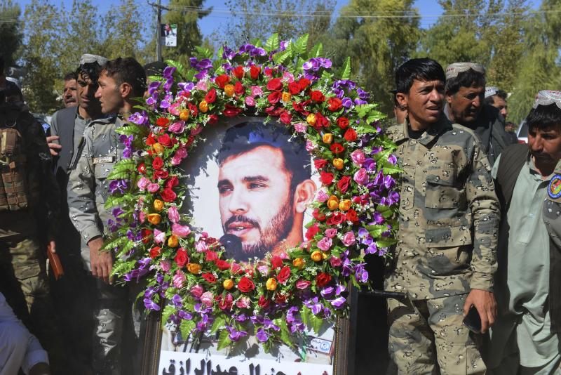 Military personnel held a photo of Gen. Abdul Raziq, Kandahar police chief, who was killed by a guard, during his burial ceremony in Kandahar, Afghanistan, Friday, Oct. 19, 2018. Afghanistan's election commission on Friday postponed elections in Kandahar for a week, following a brazen attack on a high-profile security meeting there with a U.S. delegation that killed at least two senior provincial officials, including the province's police chief. (AP Photo)