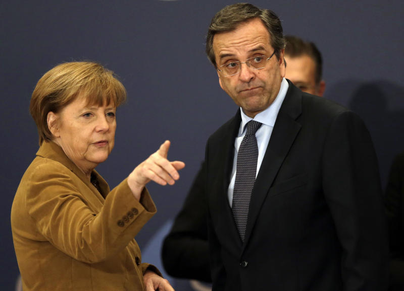 Greece's Prime Minister Antonis Samaras, right, listens to German Chancellor Angela Merkel before a meeting with young Greek businessmen in Athens on Friday, April 11, 2014. Merkel arrived for a brief visit, a day after the crisis-hit country returned to international bond markets. Greece this week reached a milestone in the recovery from its financial crisis — it successfully tapped bond markets for the first time since 2010, raising 3 billion euros ($4.14 billion) in five-year debt. (AP Photo/Thanassis Stavrakis)