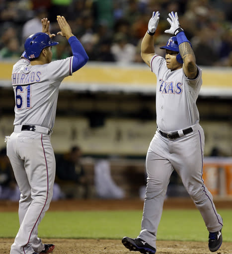 Texas Rangers' Michael Choice, right, is congratulated by Robinson Chirinos, left, after Choice hit a two run home run off Oakland Athletics' Ryan Cook in the fifth inning of a baseball game Monday, June 16, 2014, in Oakland, Calif. (AP Photo/Ben Margot)