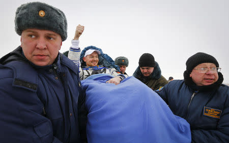Ground personnel carry International Space Station (ISS) crew member Alexander Gerst of Germany (C) shortly after landing near the town of Arkalyk in northern Kazakhstan November 10, 2014. REUTERS/Shamil Zhumatov