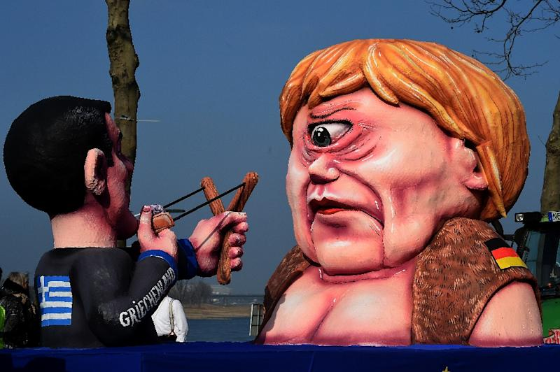 Figures depicting Greek Prime Minister Alexis Tsipras and German Chancellor Angela Merkel are pictured during the traditional rosemonday carnival parade in the western German city of Duesseldorf on February 16, 2015 (AFP Photo/Patrik Stollarz)