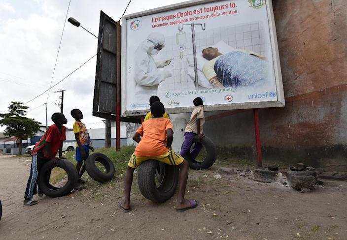 Children look at a poster warning of the dangers of the Ebola virus on August 24, 2014 in Abidjan, Ivory Coast (AFP Photo/Sia Kambou)