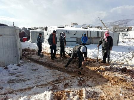 Syrian refugees work near tents at a makeshift camp at the Lebanese border town of Arsal