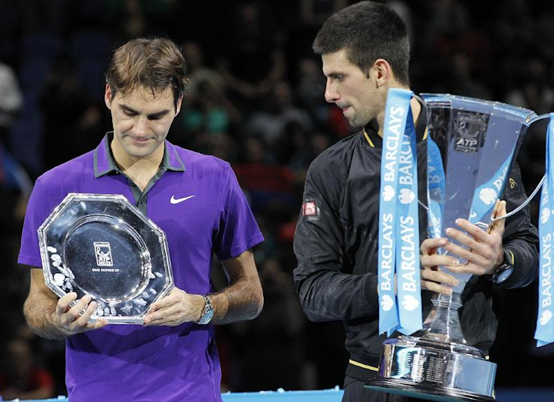 Novak Djokovic, right, of Serbia holds the winners ATP World Tour tennis trophy as he stand next to runner-up Roger Federer of Switzerland as they pose for the photographers following their singles final match in London, Monday, Nov. 12, 2012. (AP Photo/Sang Tan)