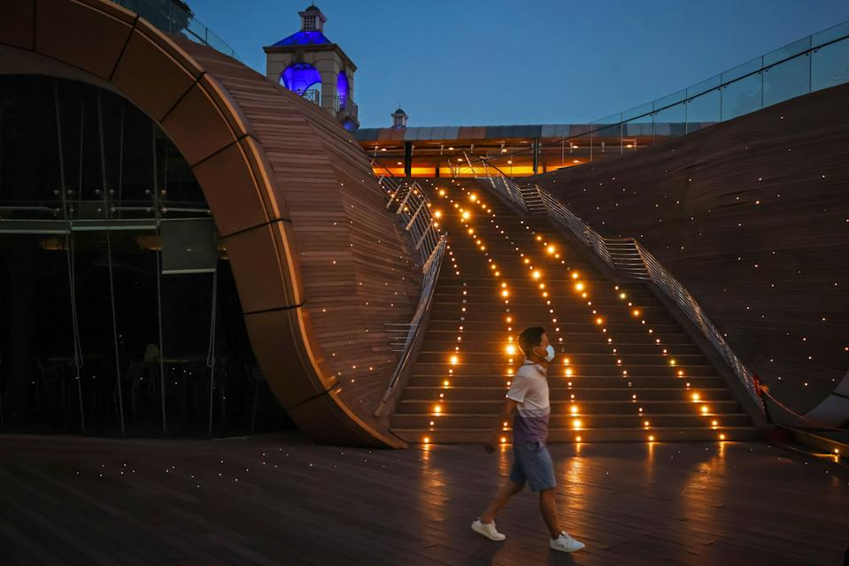 A pedestrian wearing a protective face mask walks on a boardwalk in Singapore.